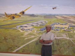 Arni Olsen stands in front of mural of No. 2 Bombing and Gunnery School.