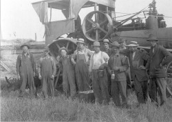 Group of ten men posing in front of early tractor.